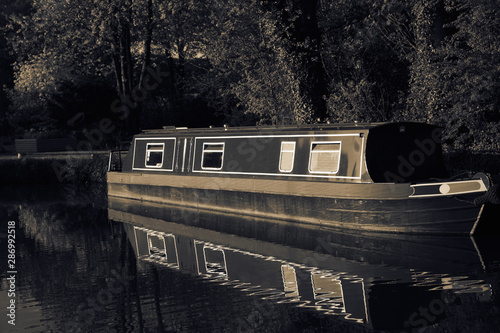 Canal barge boat moored on the Shropshire Union Canal, reflected in the water Fototapete