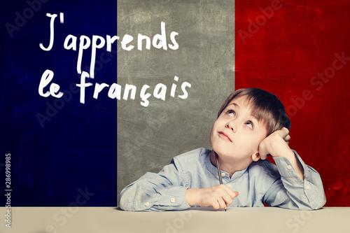 Obraz Learn french language concept. Happy child student and tittle