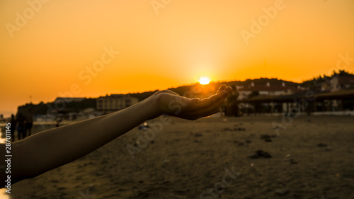 Female hand holding sun on beach sunset. Allegorical picture. Fototapeta