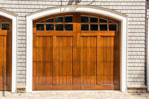 Stained wood custom garage doors for large southern home with curb appeal Wallpaper Mural