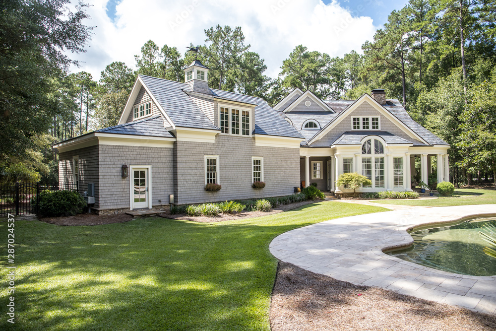 Fototapety, obrazy: Rear view and backyard of large cape cod style home with columns and windows and a round porch patio