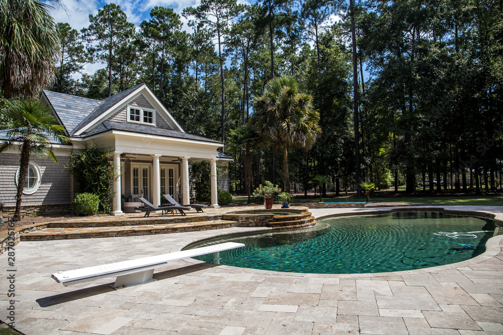 Fototapeta Custom pool House behind a landscaped estate with a large swimming pool and hot tub