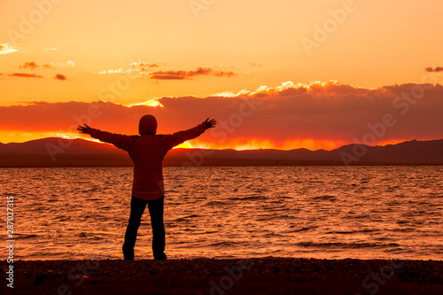 Foto auf AluDibond Ziegel Silhouette with arms outstretched towards sunset over the lake.