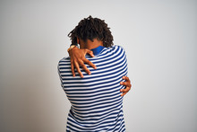 Afro Man With Dreadlocks Wearing Striped Blue Polo Standing Over Isolated White Background Hugging Oneself Happy And Positive From Backwards. Self Love And Self Care