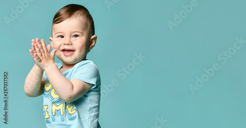 Full length portrait of a toddler boy in a blue summer cotton suit isolated in a turquoise background Canvas Print