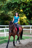 Fototapeta Konie - Young beautiful brunette girl riding on a horse.