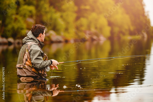 Fisherman using rod fly fishing in mountain river summer splashing water Canvas-taulu