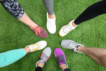 Closeup Of Athletes Wearing Sports Shoes And Standing In Circle On Green Grass, Top View