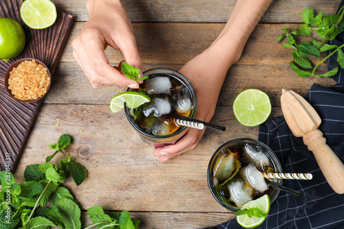 Fotomural  Woman decorating freshly made cocktail with mint at wooden table, top view