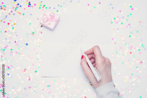 Fotografía  Woman writing a letter, gift box with pink ribbon, white desk with scattered tin
