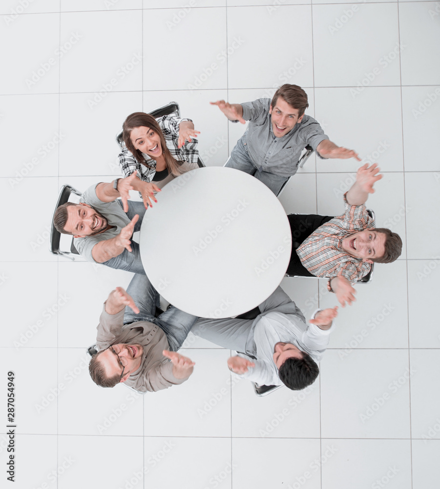 Fototapeta top view. business team holding up their hands and looking at the camera