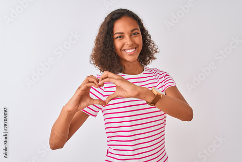 Fotografie, Obraz Young brazilian woman wearing pink striped t-shirt standing over isolated white background smiling in love doing heart symbol shape with hands