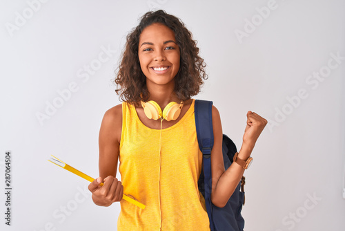 Brazilian student woman wearing backpack holding notebook over isolated white background screaming proud and celebrating victory and success very excited, cheering emotion