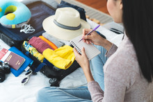 Preparing Suitcase For Summer Vacation Trip. Young Woman Checking Accessories And Stuff In Luggage On The Bed At Home Before Travel.