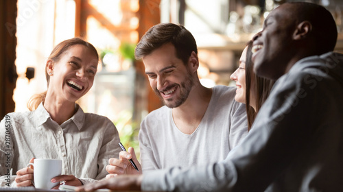 Fototapeta Happy multiracial young friends relax together talking laughing in cafe obraz