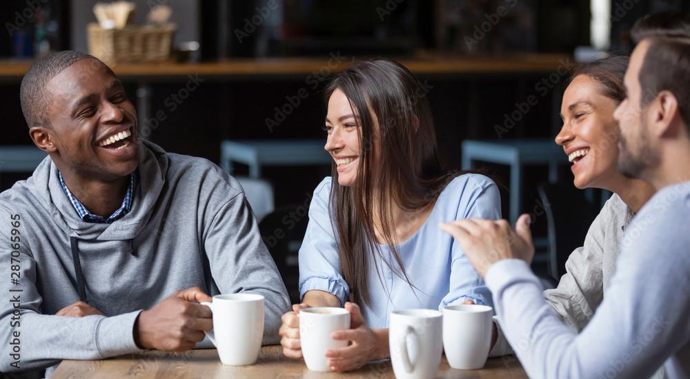 Fototapeta Multiracial friends girls and guys having fun laughing drinking coffee