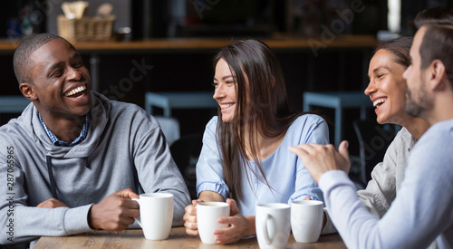 Multiracial friends girls and guys having fun laughing drinking coffee