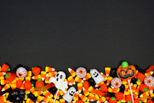 Halloween Candy Bottom Border. Top View On A Black Background With Copy Space.