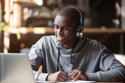 Foto  Smiling african young man student wearing headphones study online