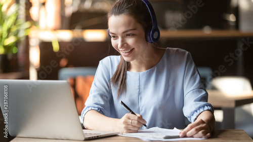 Photo Stands Coffee bar Smiling girl wear wireless headphone study online with skype teacher