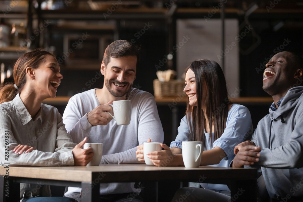 Fototapeta Happy multiracial friends group chatting laughing drink tea in cafe