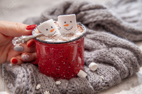Fototapeta Red mug with hot chocolate with melted marshmallow snowman in a woman hands obraz