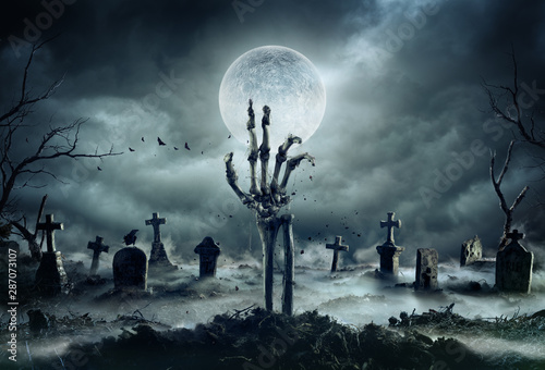 Fotografia  Skeleton Zombie Hand Rising Out Of A GraveYard - Halloween