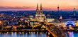 Beautiful night landscape of the gothic Cologne cathedral, Hohenzollern Bridge and the River Rhine at sunset and blue hour in Cologne, Germany