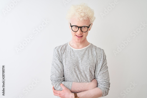 Valokuvatapetti Young albino blond man wearing striped t-shirt and glasses over isolated white background happy face smiling with crossed arms looking at the camera