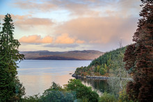 Calm Water Reflects The Orange Clouds At Sunset Near Stonefield Castle In Argyll And Bute Scotland United Kingdom