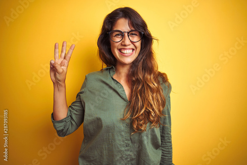 Young beautiful woman wearing green shirt and glasses over yelllow isolated background showing and pointing up with fingers number three while smiling confident and happy Tablou Canvas