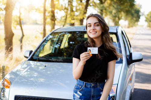 Teenader is happy to receive driving licence. Concept of buying first car