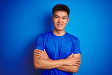 Young Asian Chinese Man Wearing T-shirt Standing Over Isolated Blue Background Happy Face Smiling With Crossed Arms Looking At The Camera. Positive Person.