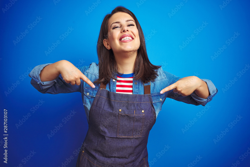 Fototapeta Young beautiful business woman wearing store uniform apron over blue isolated background looking confident with smile on face, pointing oneself with fingers proud and happy.