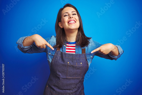 Young beautiful business woman wearing store uniform apron over blue isolated background looking confident with smile on face, pointing oneself with fingers proud and happy Fototapeta