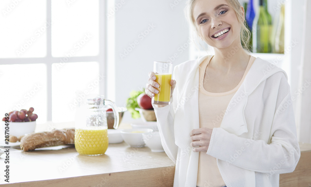 Fototapety, obrazy: Attractive woman holding a glass of orange juice while standing in the kitchen