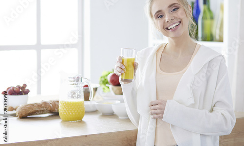 Foto  Attractive woman holding a glass of orange juice while standing in the kitchen