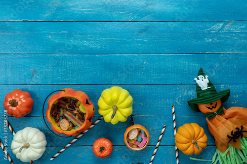 obraz dibond Table top view aerial image of decoration Happy Halloween day background concept.Flat lay accessories essential object to party the pumpkin & doll and candy on white wooden.Space for creative design.