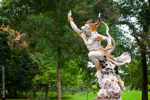 Carta da parati Ancient statue of fighting Hanuman from epic Hindu legend Ramayana in Bedugul botanical garden