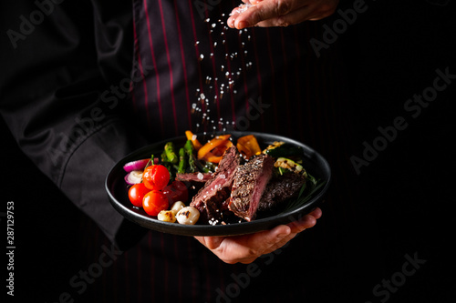 Grilled and sliced beef steak with grilled vegetables served on black plate on b Fototapet