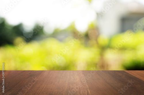 Fototapeta Wooden tabletop in front of blurred green nature background. obraz na płótnie