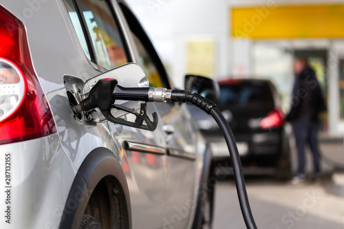 gray metallic car refueling on gas station - closeup with selective focus and bl Wallpaper Mural