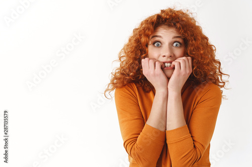 Photo  Scared young redhead curly-haired woman biting fingers, trembling fear, realise