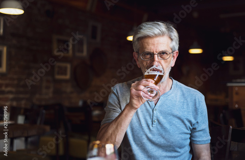 Photo Senior man having a beer in the bar