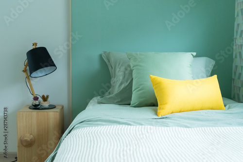 Vászonkép  Contemporary teen bedroom with green pillow and modern side table lamp