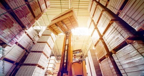 Obraz Forklift loader in storage warehouse ship yard. Distribution products. Delivery. Logistics. Transportation. - fototapety do salonu
