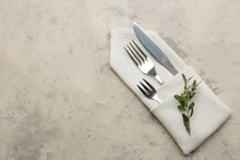 Table Setting. Cutlery. Fork, Knife In A White Napkin On A Light Concrete Table. Top View
