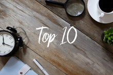 Top View Of Clock,notebook,pen, Magnifying Glass, A Cup Of Coffee And Plant On Wooden Background Written With Top 10.