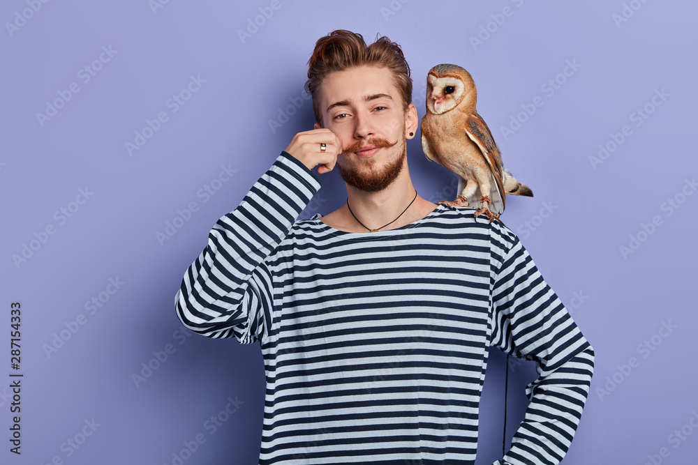 Fototapety, obrazy: cheerful funny cunning guy in striped sweater taking money from tourist for taking a pictire with an owl, isolated blue background, studio shot, business concept