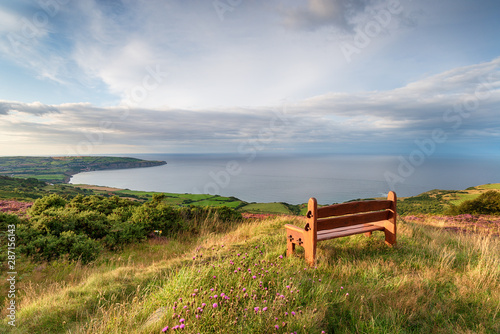 A wooden bench facing out to sea above Ravenscar on the Yorkshire coast Fotobehang